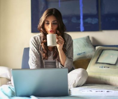 woman-in-grey-jacket-sits-on-bed-uses-grey-laptop-935743